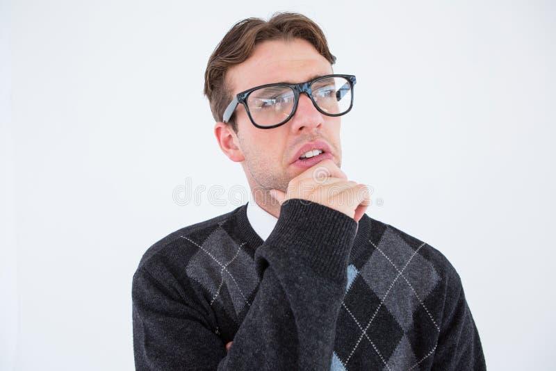 Inconformista Geeky que piensa con la mano en la barbilla foto de archivo libre de regalías
