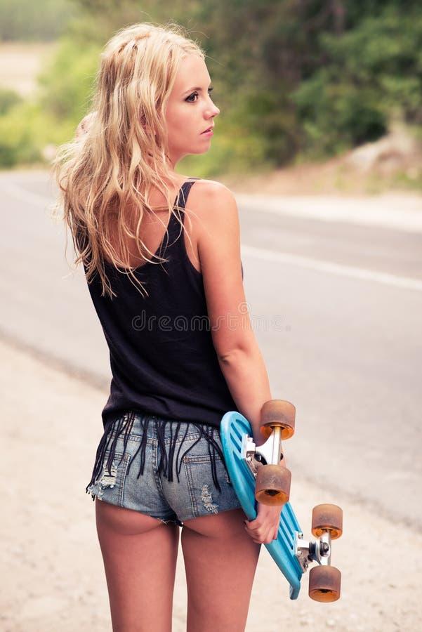 Inconformista hermoso de la chica joven con andar en monopatín imagenes de archivo