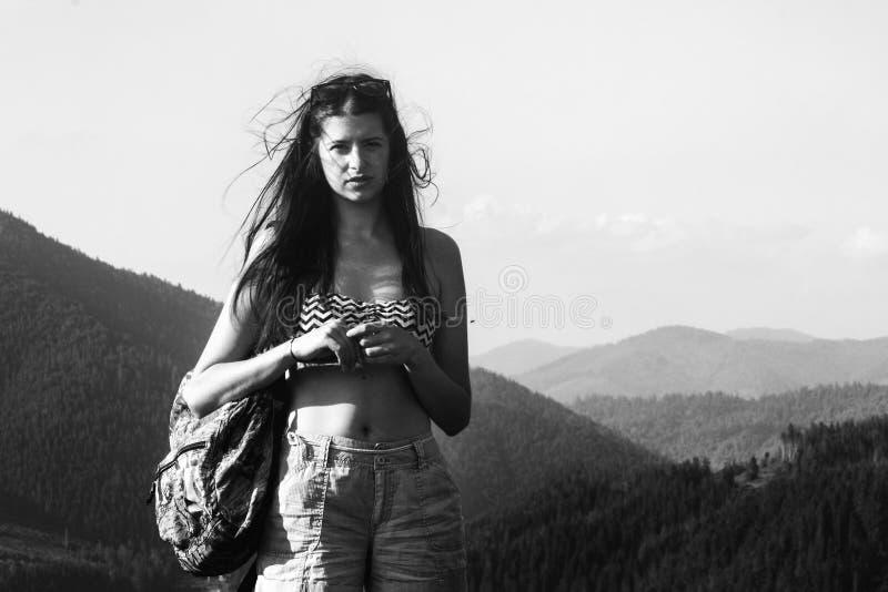 Inconformista hermoso feliz de la muchacha que viaja en la colina superior en el fondo del cielo y de montañas asombrosos en vera foto de archivo libre de regalías