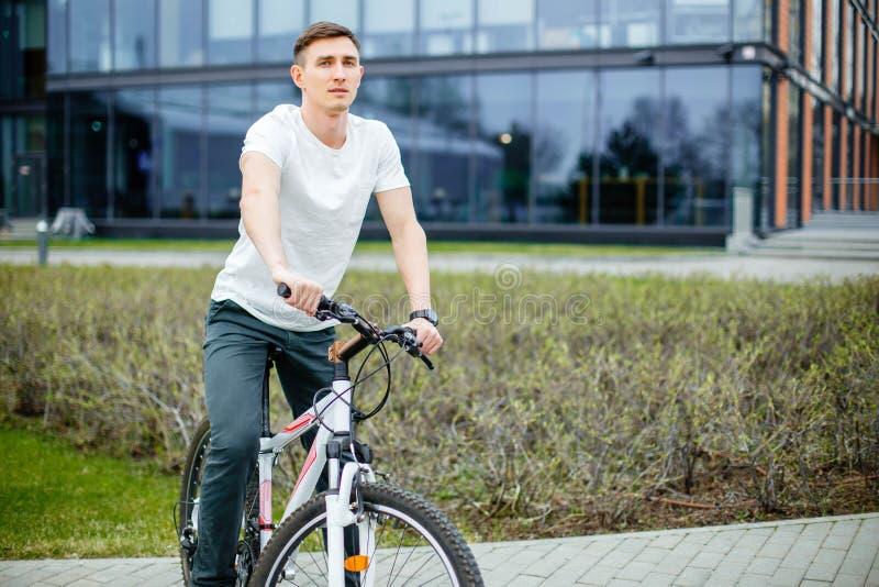 Inconformista hermoso que disfruta de paseo de la ciudad en bicicleta foto de archivo