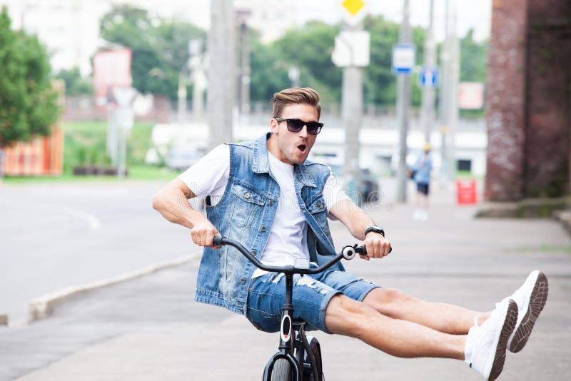 Inconformista hermoso que disfruta de paseo de la ciudad en bicicleta imagenes de archivo