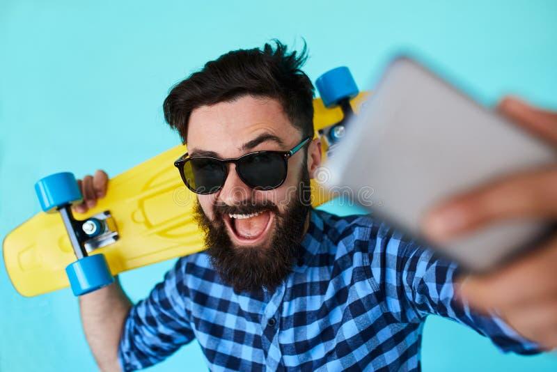 Inconformista joven con la barba en los vidrios que toman el selfie y la sonrisa aislados en el fondo blanco en blanco fotos de archivo
