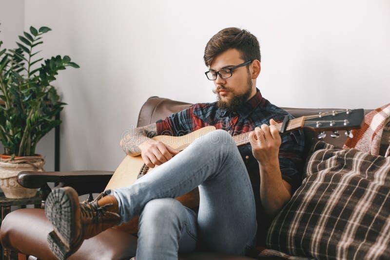 Inconformista joven del guitarrista en casa con la guitarra que se sienta jugando el primer relajado imagenes de archivo