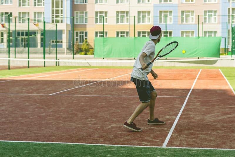 Inconformista joven en la corte el jugador de tenis casual imagen de archivo