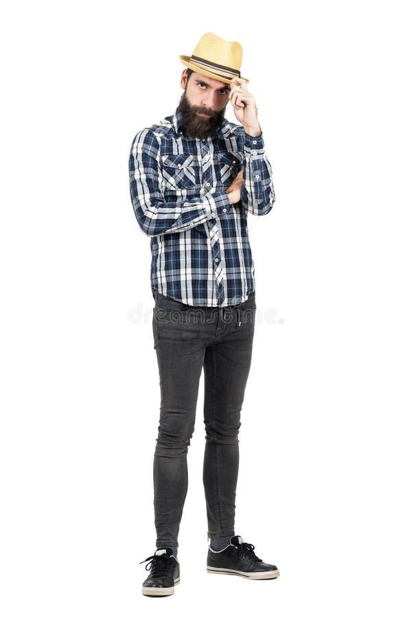 Inconformista joven serio que sostiene el visera del sombrero de paja que mira la cámara fotos de archivo