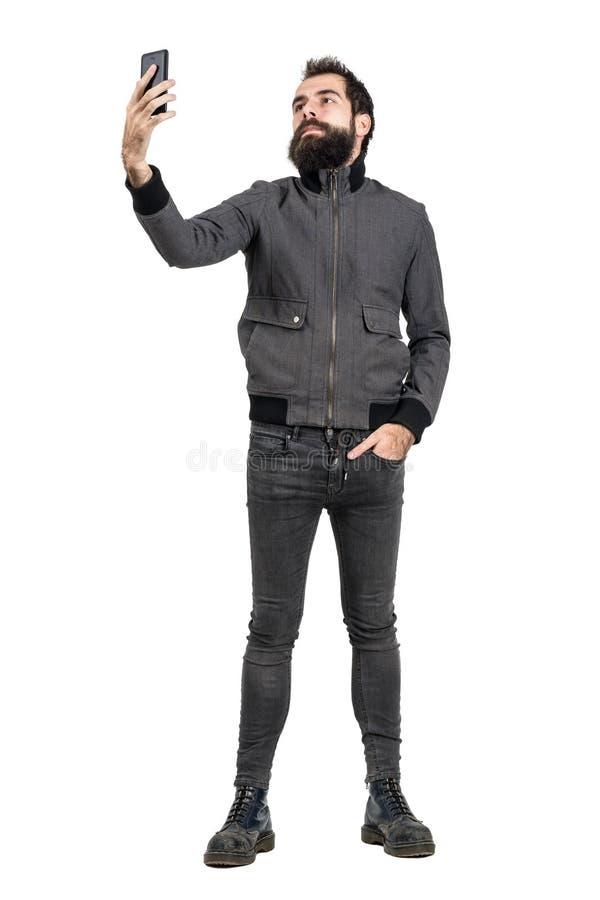 Inconformista o punker confiado serio que toma el autorretrato del selfie con el teléfono móvil fotos de archivo libres de regalías