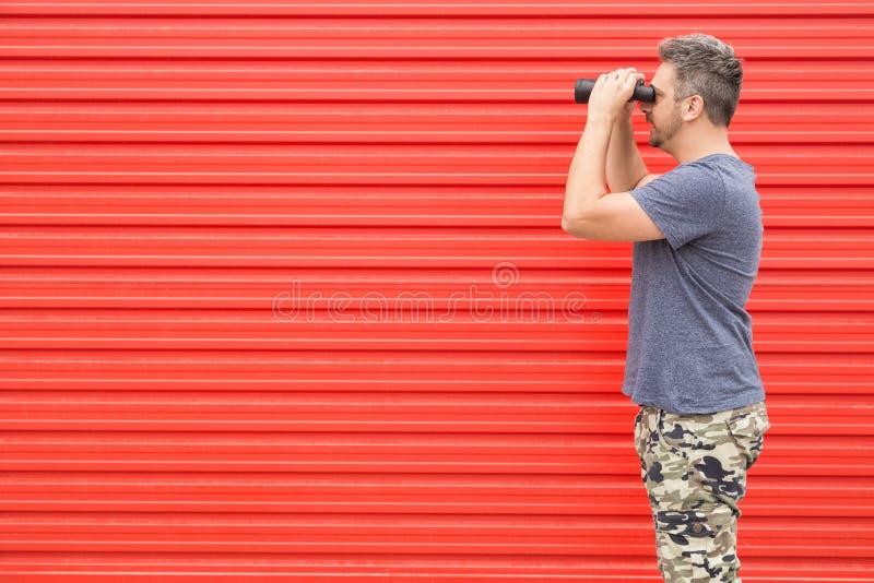 Inconformista que usa los prismáticos en fondo rojo imagenes de archivo