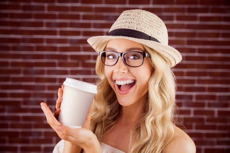 Inconformista rubio sonriente magnífico que presenta la taza para llevar fotos de archivo libres de regalías