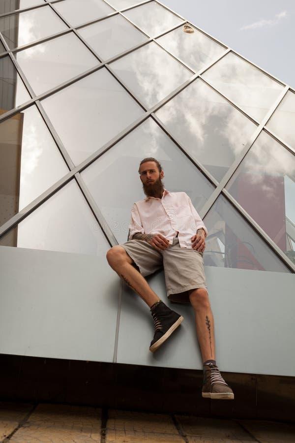 Inconformista tatuado barbudo fresco que presenta delante del edificio de oficinas fotos de archivo libres de regalías