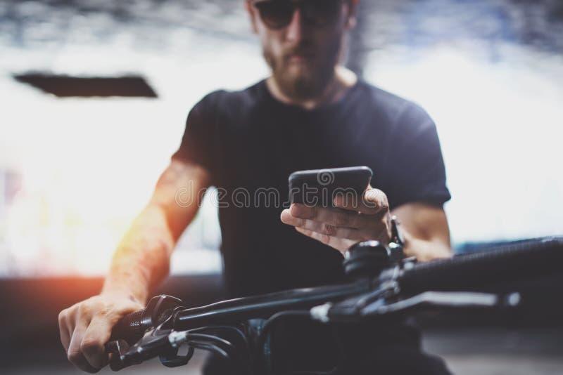 Inconformista tatuado muscular barbudo en gafas de sol usando smartphone después de montar en vespa eléctrica en la ciudad foto de archivo libre de regalías