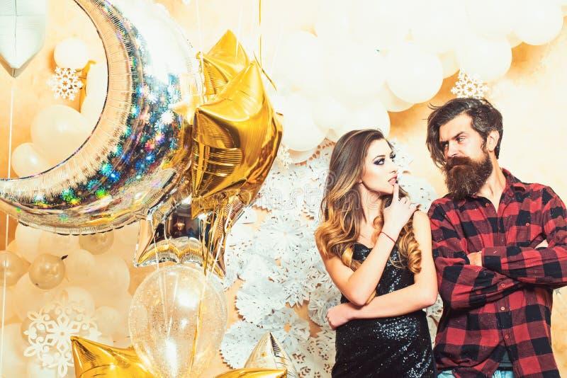 Inconformista y mujer el A?o Nuevo o v?spera de Navidad Mujer sensual y hombre barbudo con los globos del partido, la Navidad Par foto de archivo