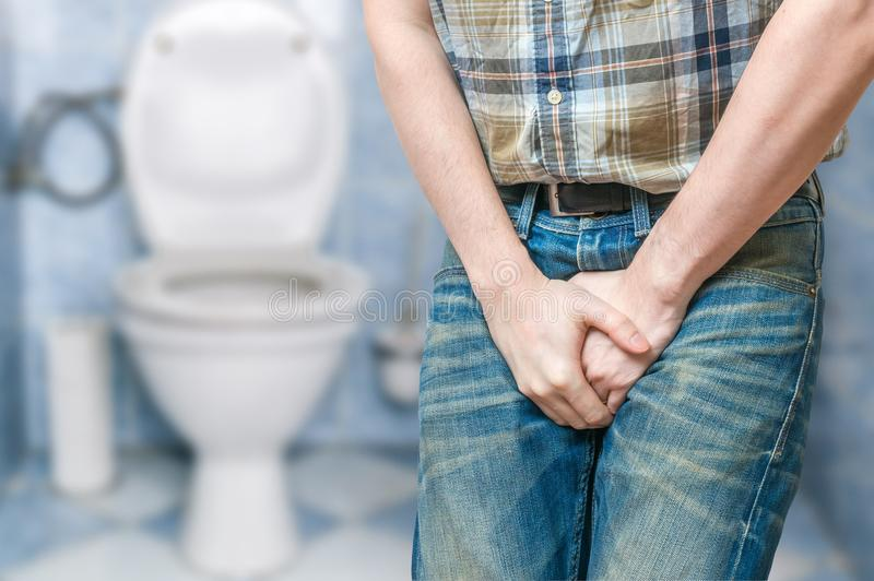 Incontinence concept. Man wants to pee and is holding his bladder.  royalty free stock image