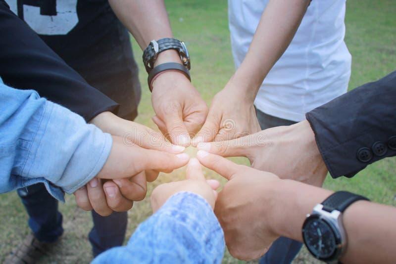 Incontrando concetto di lavoro di squadra, il gruppo di amicizia con le mani che mostrano unità ed i pollici su su fondo verde fotografie stock