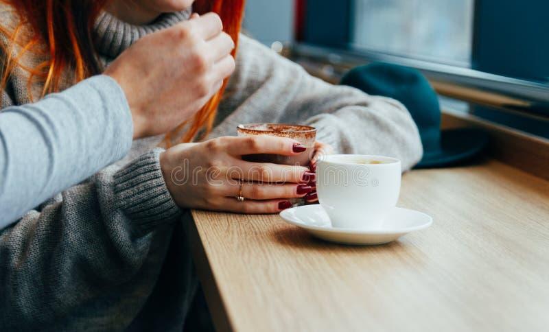 Incontrandosi ad un caffè, cioccolata calda bevente della ragazza dai capelli rossi immagini stock