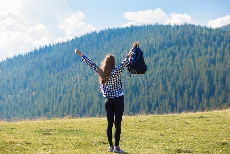 Incoraggiare della donna della viandante esaltato e beato con le armi alzate in cielo dopo l'escursione alla cima della montagna fotografia stock