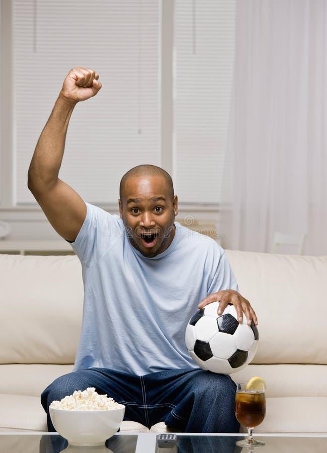 Incoraggiare della sfera di calcio della holding dell'uomo immagine stock