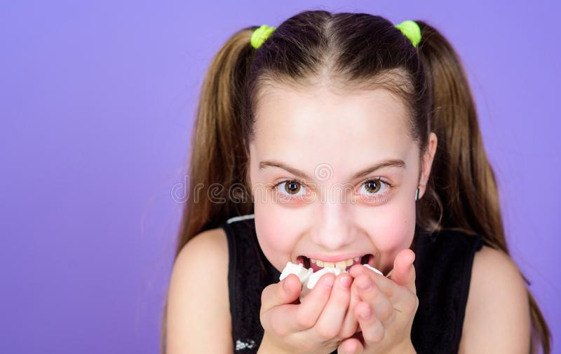 Incorrigible sweet tooth. Girl smiling face holds sweet marshmallows in hand violet background. Sweet tooth concept. Kid. Girl with long hair likes sweets and royalty free stock photos