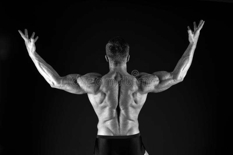 Increasing muscle mass through exercise. Muscle man back view on black background. Strong sportsman raising arms with stock images