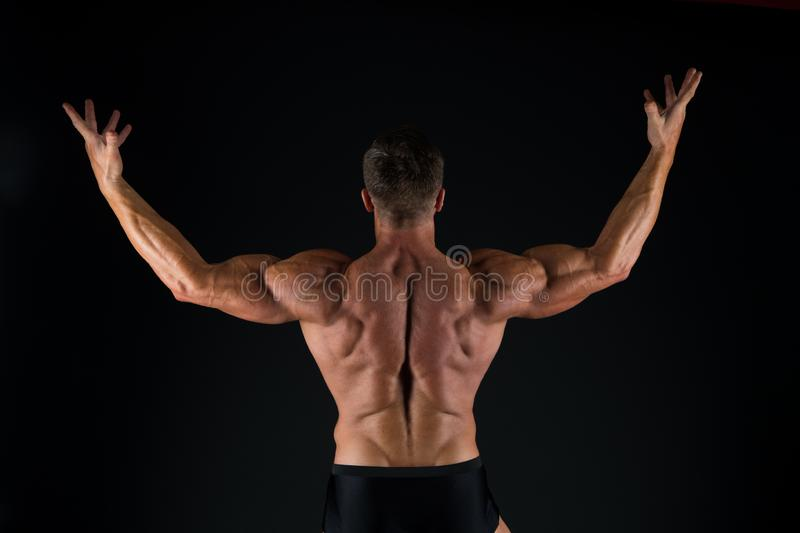 Increasing muscle mass through exercise. Muscle man back view on black background. Strong sportsman raising arms with royalty free stock image
