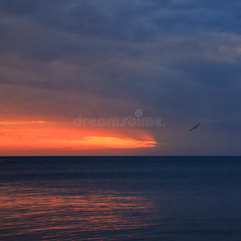 Incredible beautiful sunset. The sun goes into the sea and colors the sky in a bright orange color royalty free stock images