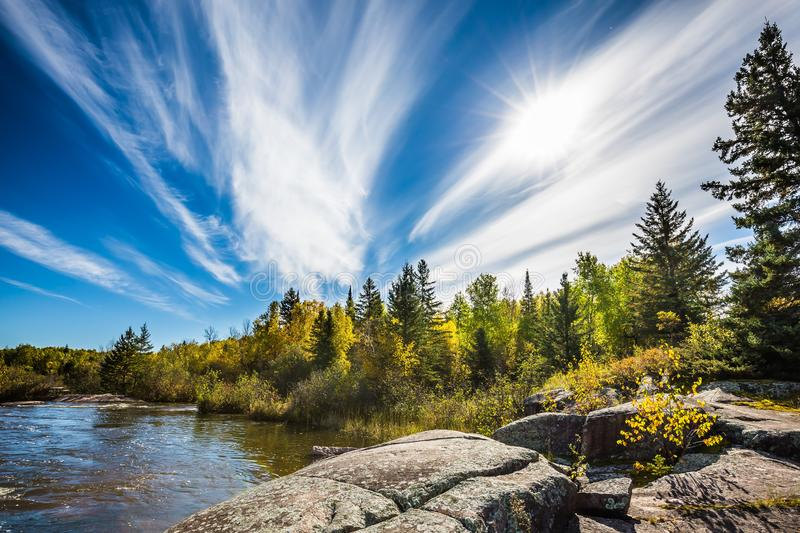 Incredible cirrus clouds  and huge flat stones in Old Pinawa Dam Park. Indian summer in Manitoba, Canada. The concept of. Ecological and recreational tourism royalty free stock photography