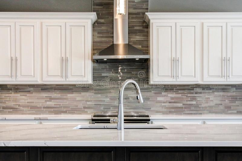 Incredible contemporary kitchen with white cabinets and glass backsplash. royalty free stock photos