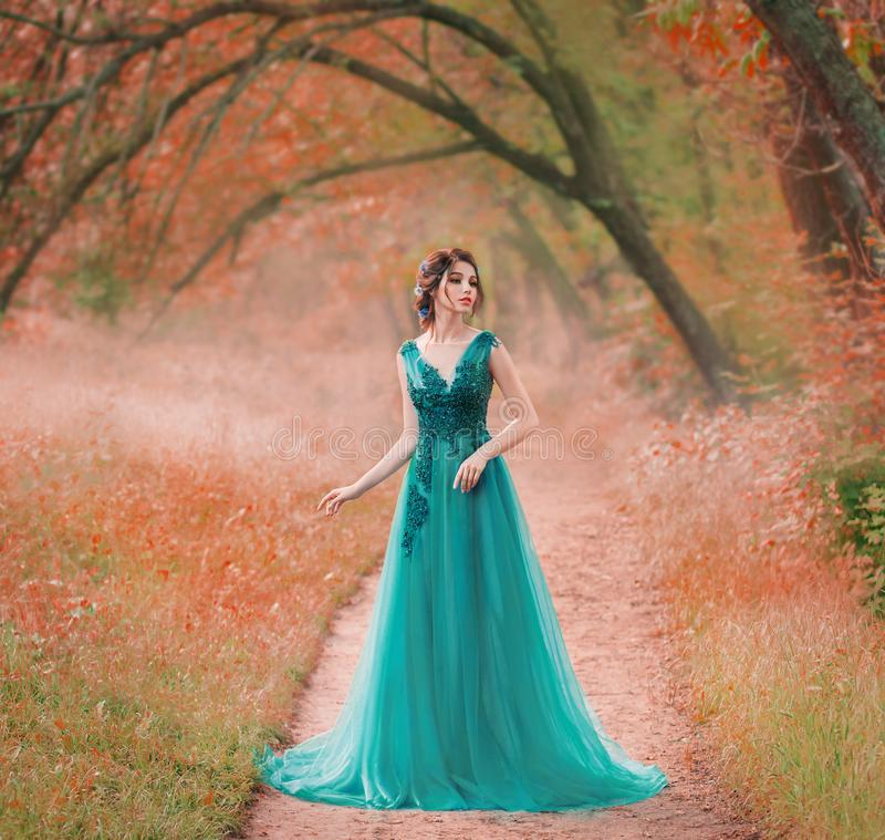 Incredible cute sea princess walks through a red fairy forest alone, a magic fairy in a green turquoise dress, a cute. Dark-haired nymph like a magic flower, a stock image