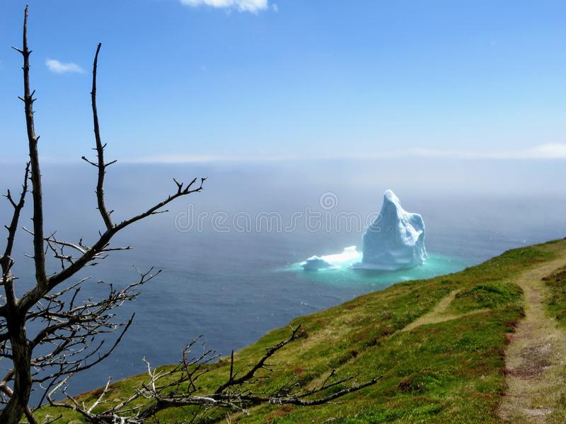 Incredible iceberg floating along the rugged coast beside the Sk. Erwink Trail in Newfoundland and Labrador, Canada royalty free stock image