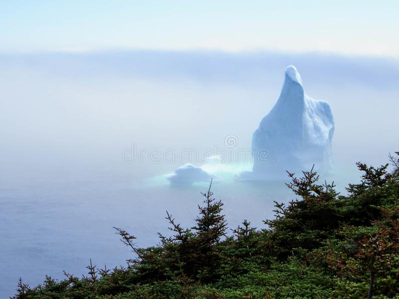 Incredible iceberg floating along the rugged coast beside the Sk. Erwink Trail in Newfoundland and Labrador, Canada royalty free stock photo