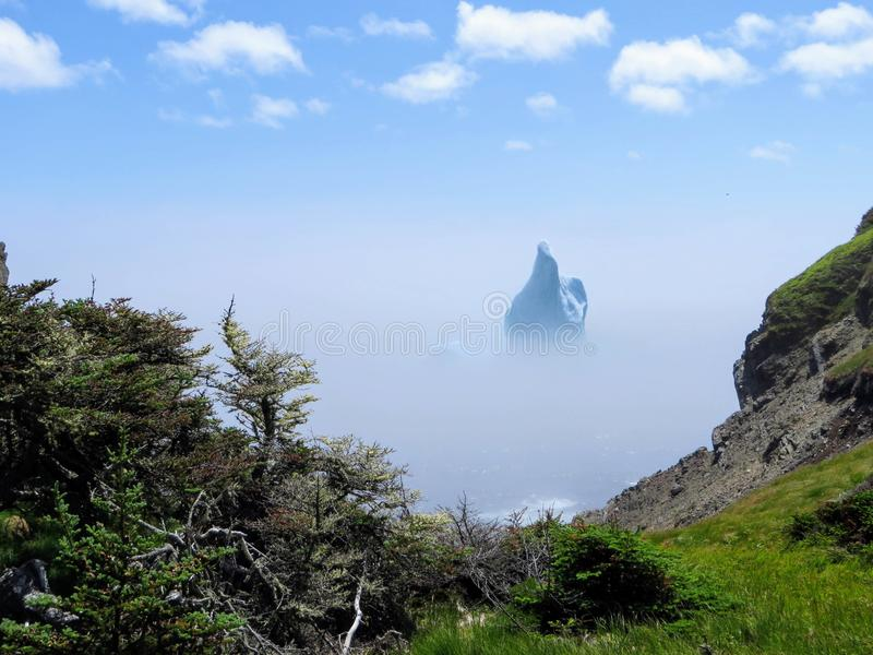 Incredible iceberg floating along the rugged coast beside the Sk. Erwink Trail in Newfoundland and Labrador, Canada royalty free stock photography