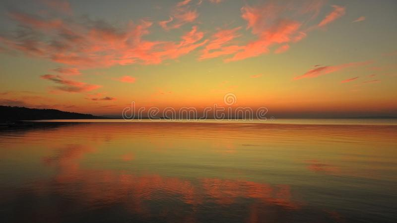 The incredible reflections of red clouds. Over sea water during sunset royalty free stock image