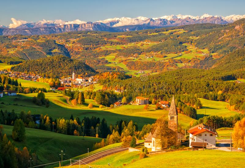 Incredible scenic view of traditional tyrol village with churches in alpine valley at autumn sunny day. Snowcaped mountain range on background. Dolomites royalty free stock photography