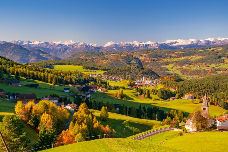 Incredible scenic view of traditional tyrol village with churches in alpine valley at autumn sunny day. Italy royalty free stock images