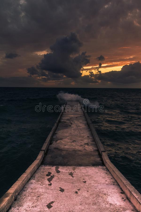 Incredible sunsets on the black sea. Clouds over sea. A splash of water. Waves. Sunset at sea. The road through horizon. pier in sea stock image