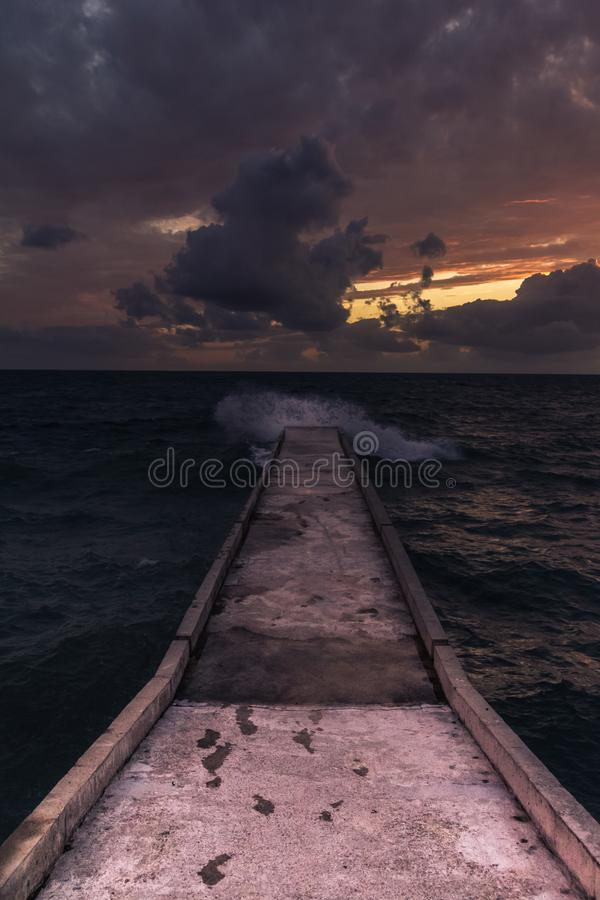 Incredible sunsets on the black sea. Clouds over sea. A splash of water. Waves. Sunset at sea. The road through horizon. pier in sea royalty free stock photo