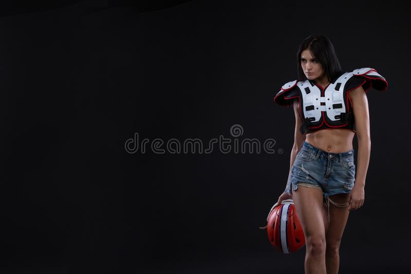 Incredibly beautiful, athletic brunette girl in a shoulderpads and an American football helmet demonstrating stunning amazing abs. stock photos