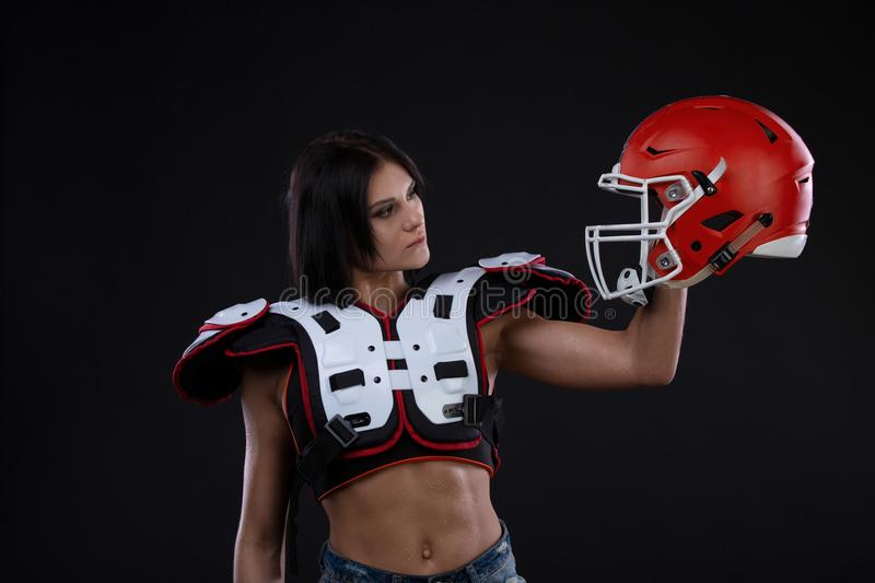 Incredibly beautiful, athletic brunette girl in a shoulderpads and an American football helmet demonstrating stunning amazing abs. stock photo