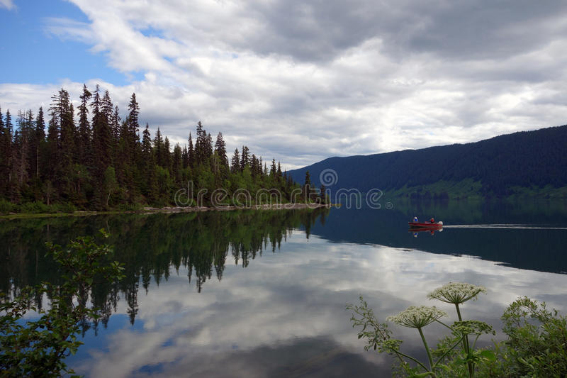 An incredibly beautiful campground at mezidian lake, brisith columbia. Pine trees, sky and clouds reflected in a glassy, calm lake at the cassiar highway, canada royalty free stock images