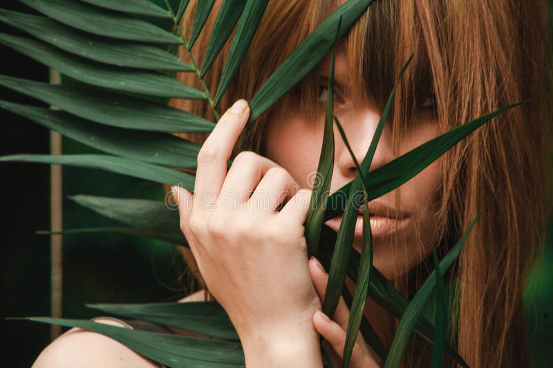 Incredibly beautiful girl covers her face with a palm branch royalty free stock photography