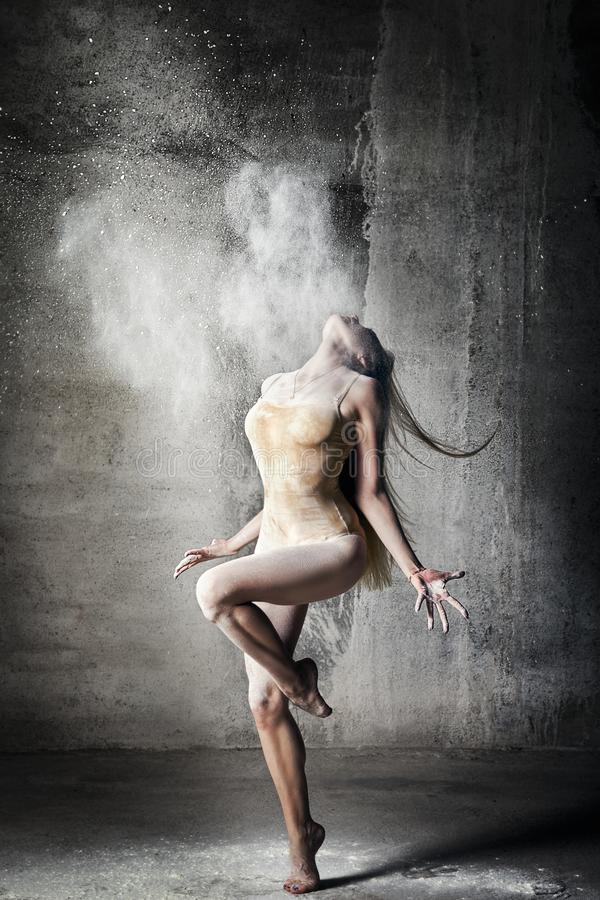 Incredibly beautiful pose of a dancer with flying flour on a gray background. Beautiful girl ballerina with blond hair. Dance, emotion, pose, feet, ballet royalty free stock photos