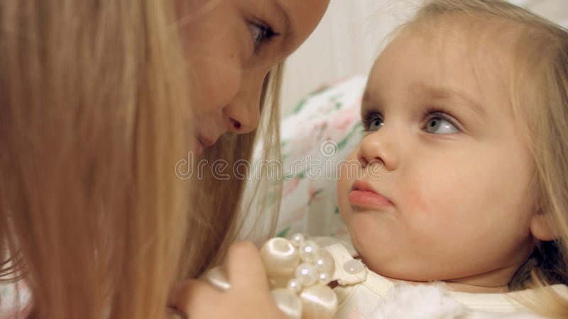 Incredibly cute sisters playing on the bed. Incredibly cute little sisters playing on the bed stock photos