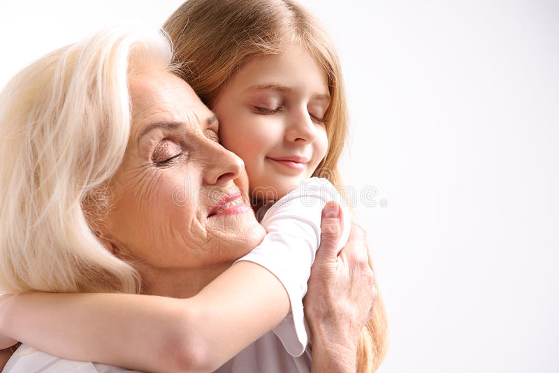 Incredibly happy female persons hugging. Absolutely happiness. Grandmother and granddaughter are embracing with closed eyes. . Copy space royalty free stock photography