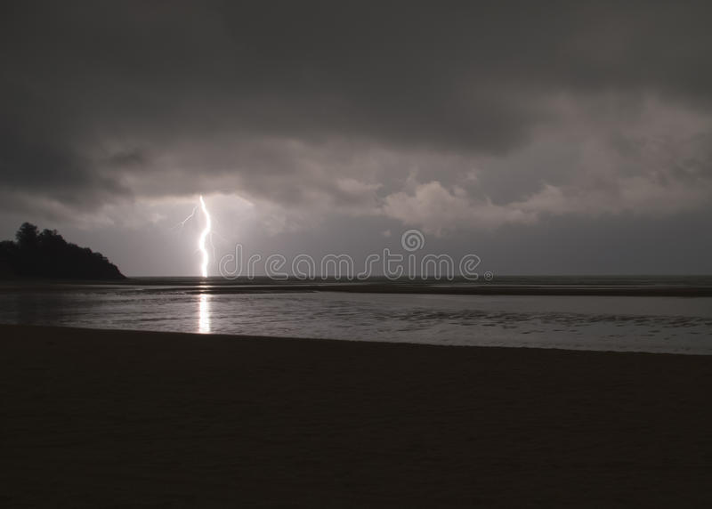 Incredibly sharp lightning with branches hitting the ocean with royalty free stock image