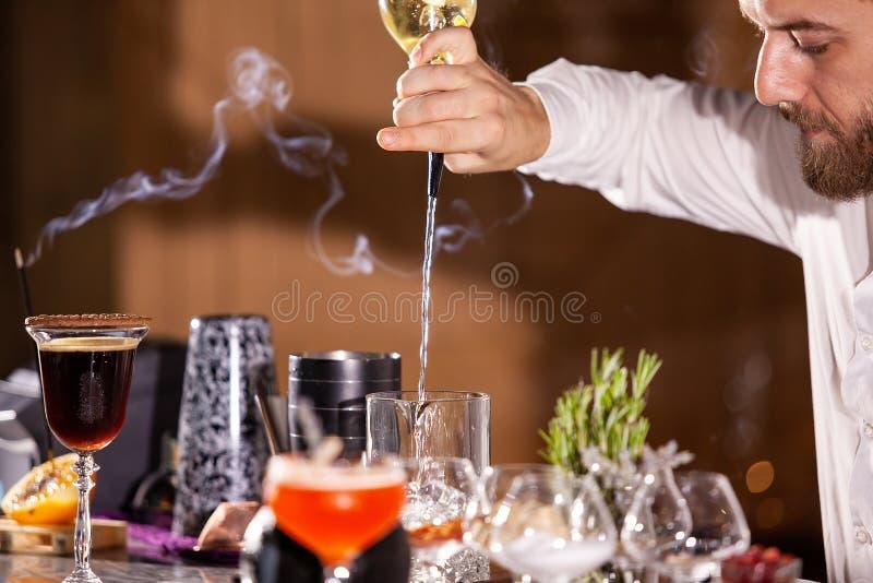 Incredients de versement de cocktail de barman images libres de droits