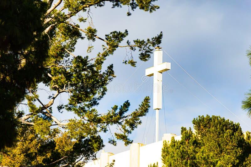 Incrocio bianco su cielo blu, con gli alberi ed il bordo della costruzione immagini stock libere da diritti