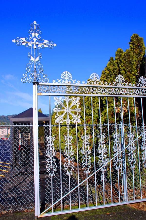 Incrocio d'argento sul portone dell'entrata del cimitero massonico, Canyonville, Oregon fotografie stock libere da diritti