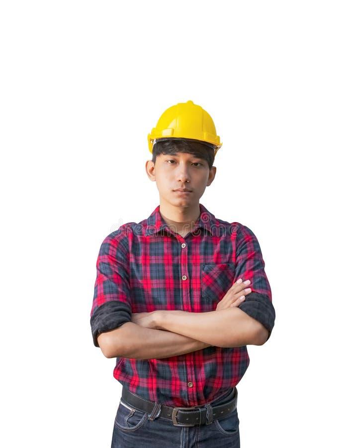 Incrocio del braccio della costruzione dell'ingegnere sul petto ed indossare la plastica gialla del casco di sicurezza su fondo b fotografie stock libere da diritti