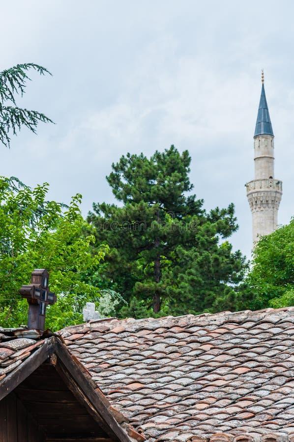 Incrocio di legno cattolico sopra il tetto su priorità alta e la torre di Mustafa Pasha Mosque sui precedenti a Skopje, Macedonia fotografia stock libera da diritti