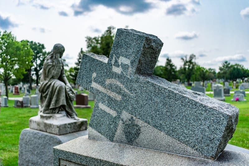 Incrocio sopra una pietra tombale ad un cimitero fotografia stock libera da diritti
