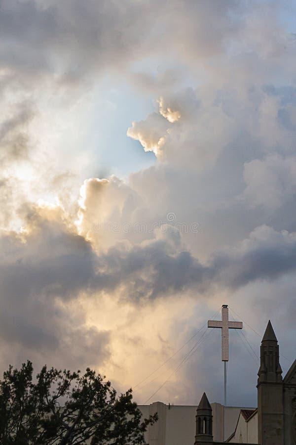 Incrocio su costruzione con le torri e gli alberi contro le grandi nuvole variopinte fotografia stock libera da diritti